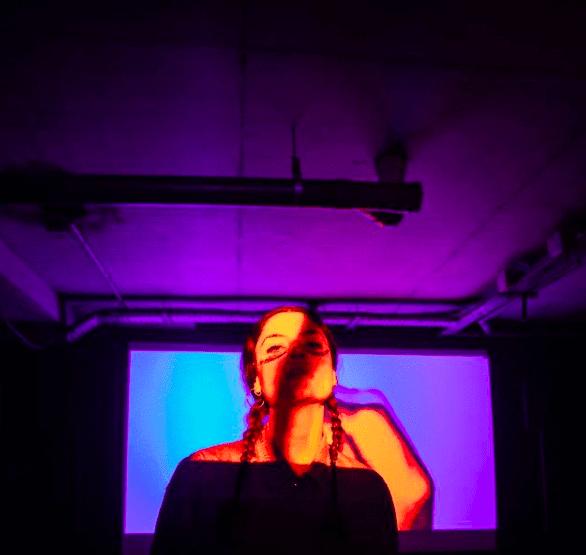 Une jeune femme devant un écran bleu.