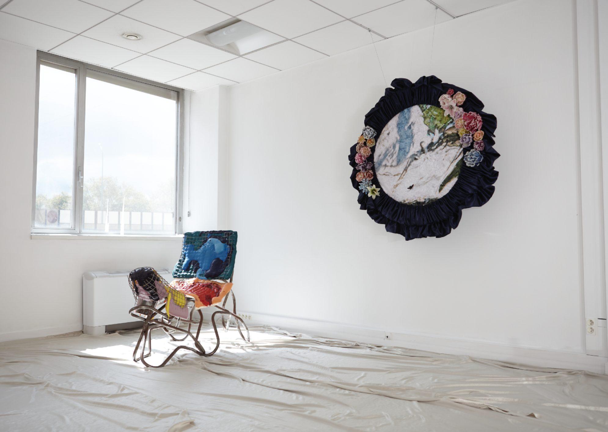 Plan d'une salle très lumineuse. Au mur, une peinture marbrée, encadrée par un tissus en velour bleu nuit parsemé de fleurs colorées. Au sol, une construction qui ressemble à une chaise est recouverte de tissus bariolés et gaufrés.