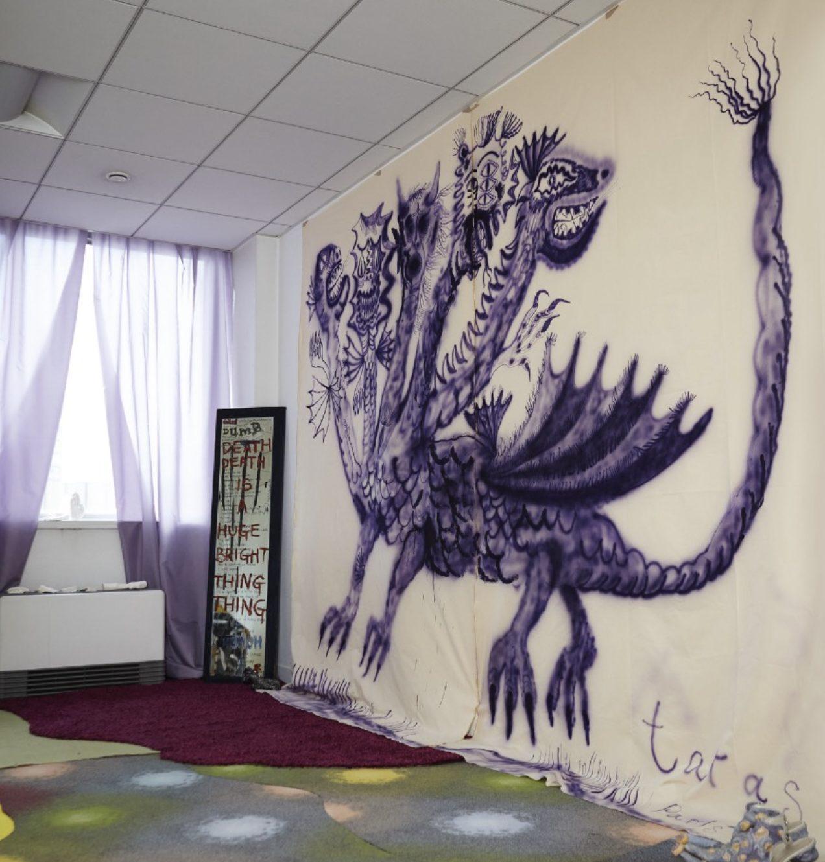 """Dernière pièce de l'exposition Beatus.  La fenêtre de cette pièce est encadrée par des voilages violets, qui font échos à un cerbère taggé au mur dans cette même couleur. Dans l'angle, un miroir sur lequel est inscrit """"Death is a huge bright thing""""."""