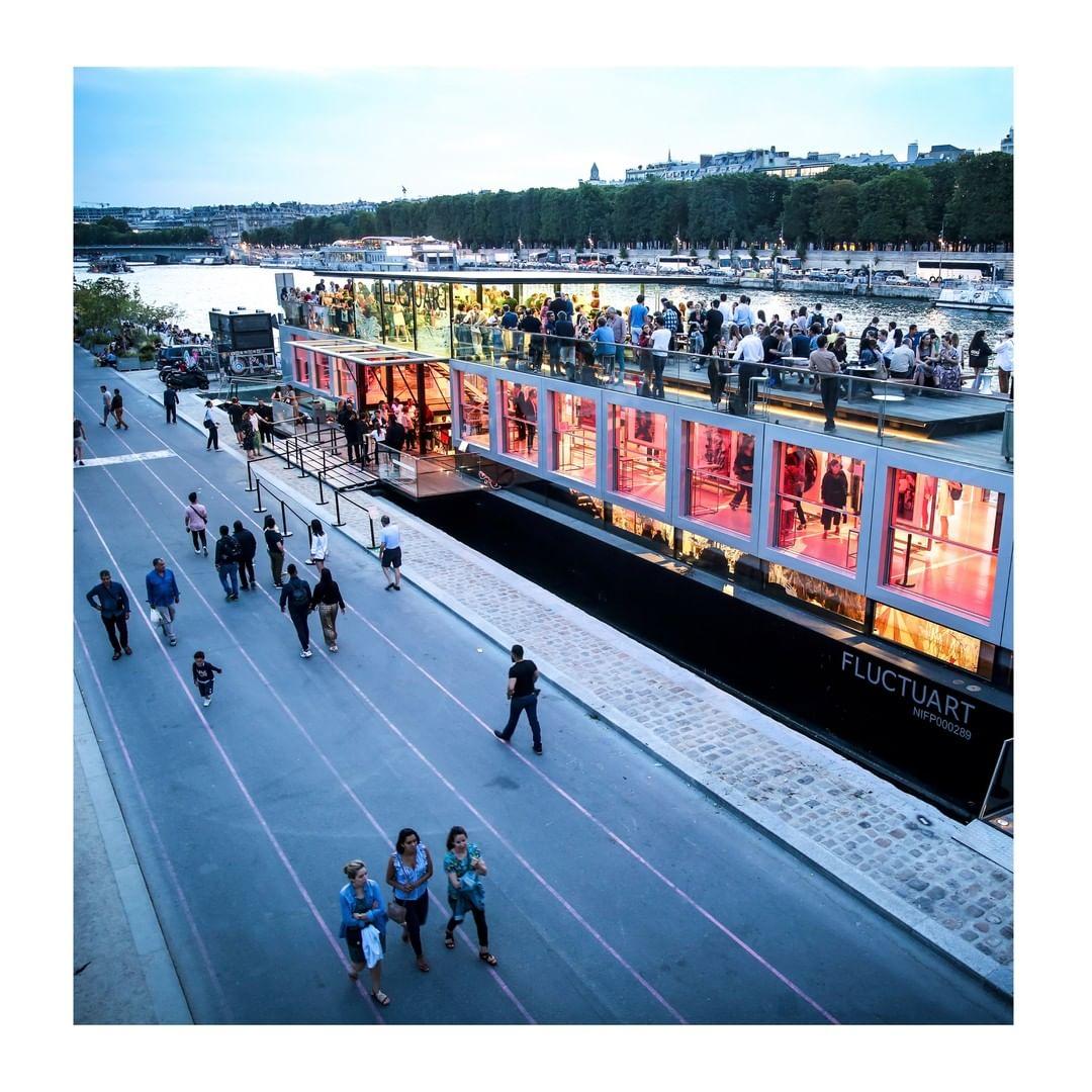 Vue en plongée de la guinguette. A gauche, des passants, à droite la guinguette aux lumières colorées et au rooftop regorgeant de clients.