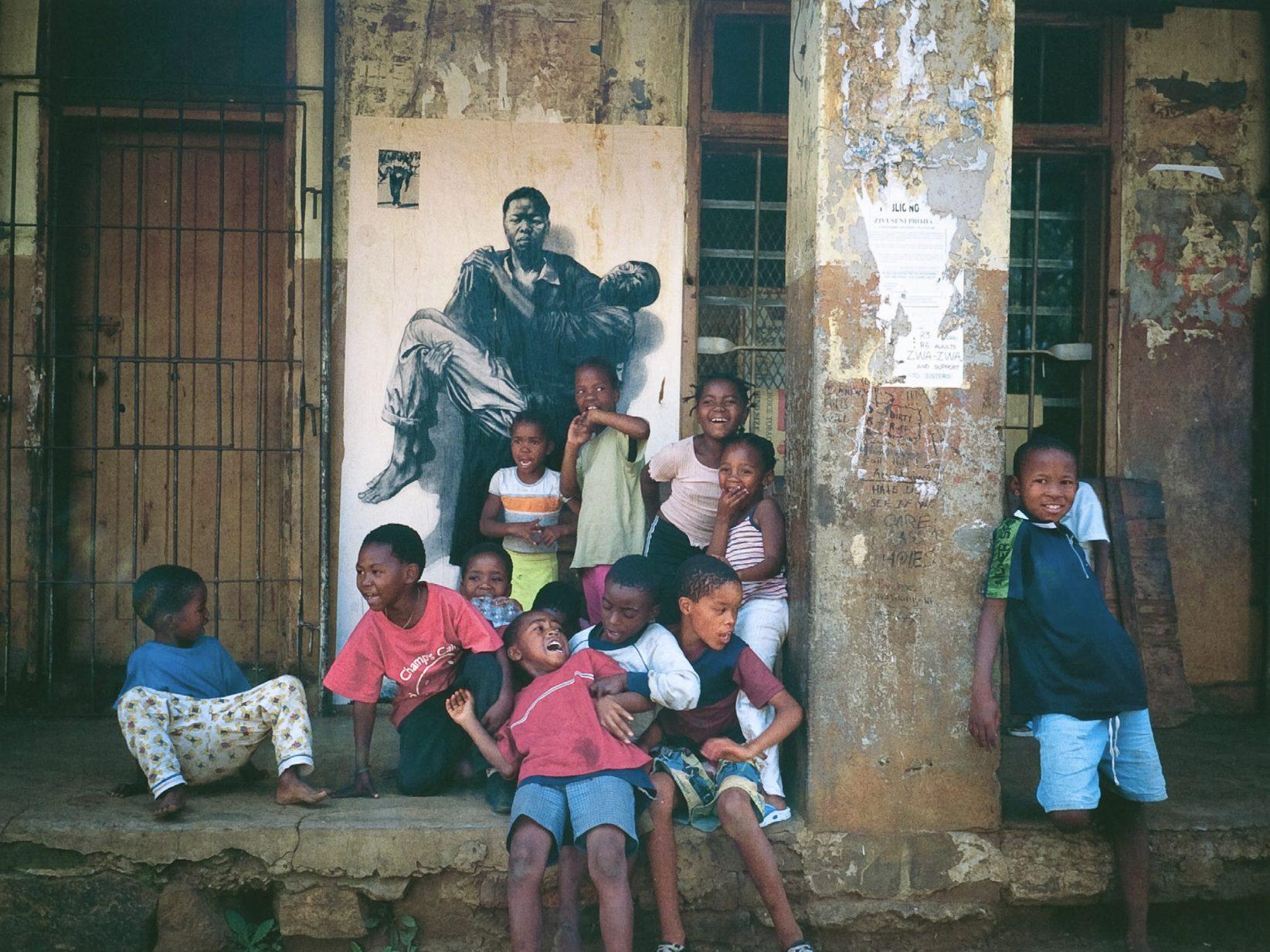 Photographie de la ville de Kliptown, en Afrique du sud. Derrière un groupe d'enfant souriants, un dessin est collé au mur. Une femme noire y porte le cadavre d'un homme.
