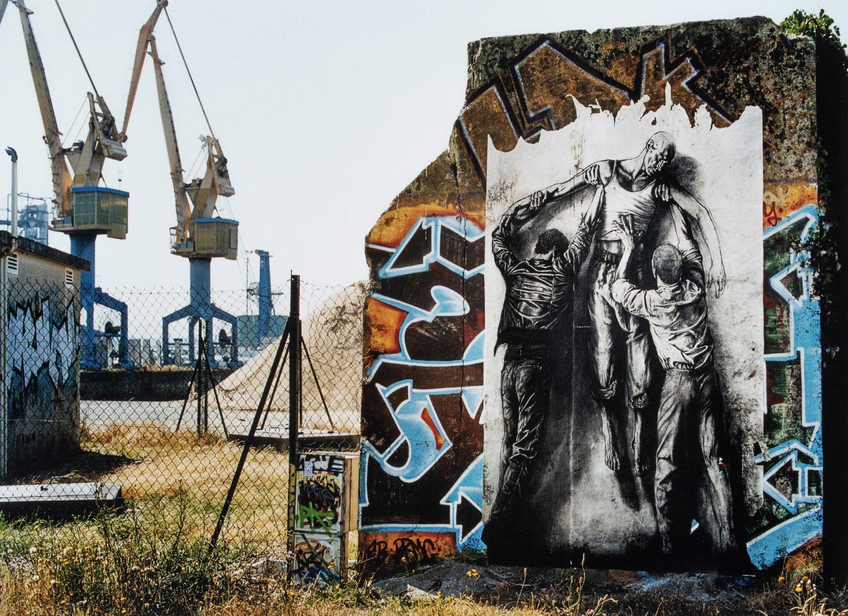 Pan de mur recouvers de graffiti, devant un grand chantier, à Brest. Collage d'un grand dessin de Jean Genet, mort, soulevé par deux hommes.