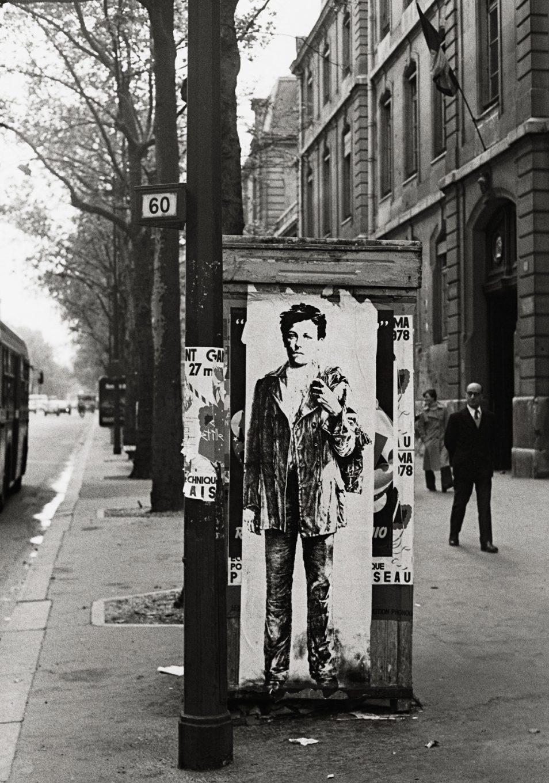 Photographie d'époque, rue de Paris. Une feuille avec un portrait du jeune Rimbaud est collée sur un bloc dans la rue.