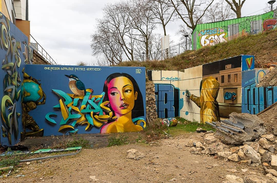 Visuel de l'espace SPOT 13, un mur à droite est le canvas d'une peinture d'un jeune graffeur, vu de dos. Le mur de droite est une fresque sur fond bleu, avec le visage d'une femme à la peau dorée et un Atlas, portant le monde sur son dos, dans l'angle.