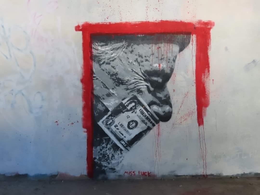 Illustration au pochoir d'un homme âgé, tête baissée, muselé par un billet américain, le tout dans un cadre de peinture rouge.
