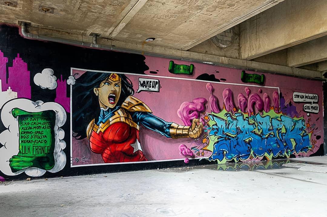 """Grand pan de mur recouvert d'un fond rose et vert et travaillé comme une case de bande-dessinée. Une figure représentant Xander Woman frappe un lot de lettres, avec une bulle lisant """"Wake up""""."""