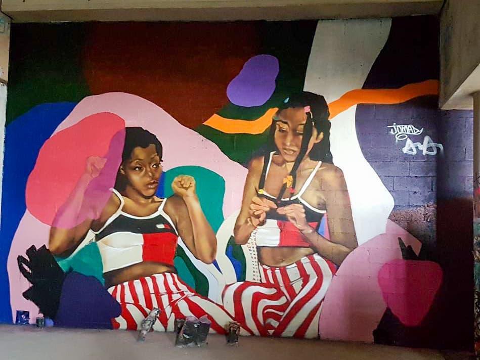 Fresque murale de deux jeunes femmes, assises ensemble. Les deux portent des vêtements assortis, et se détendent dans un espace recouvert de tâches de couleurs. Spot 13 paris