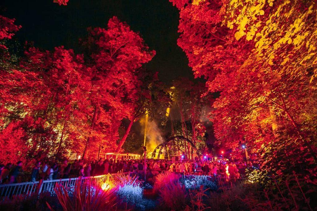 Prise de nuit, on distingue des danseurs et l'arche de la scène entre les grands arbres et une lumière rose et bleu.