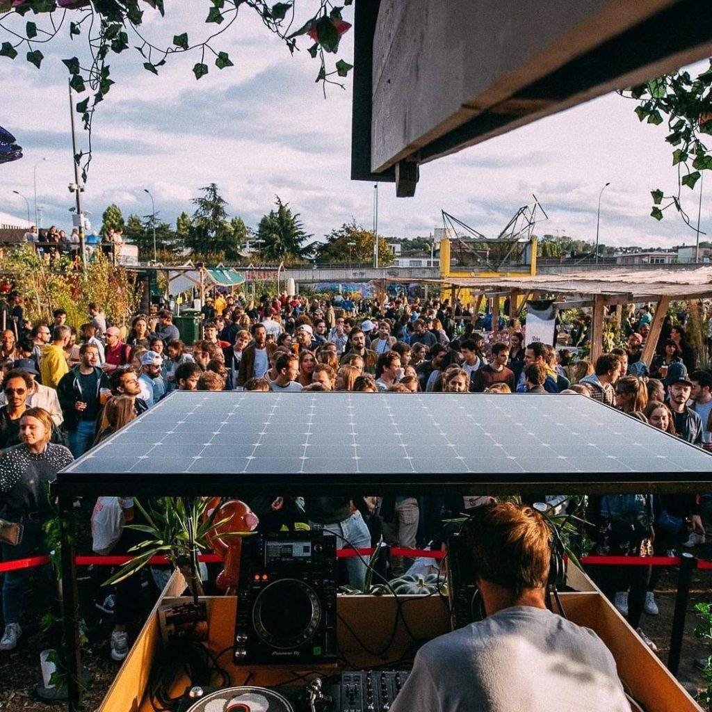 Open air à la prairie du canal. En premier plan, le DJ mixe, de dos mais face à la foule. Les danseurs baignés de soleil font face à la caméra.