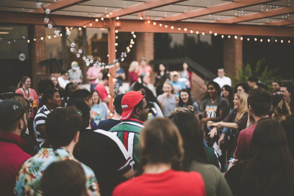 photographie d'un groupe de personnes réunies pour danser ensemble, sous un porche décoré de guirlandes lumineuses.