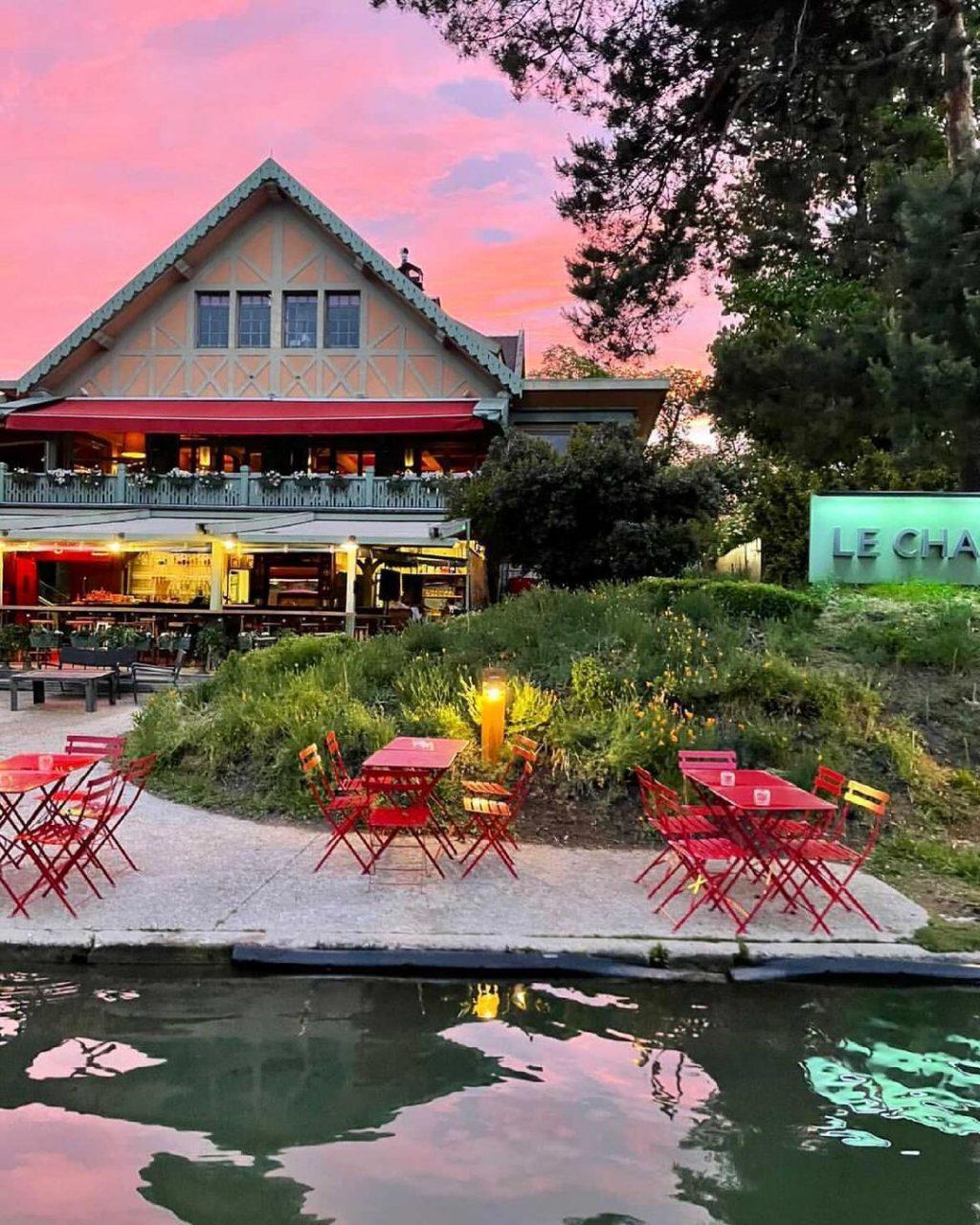 Coucher de soleil sur le chalet des îles. Une guinguette en chalet rose fait face à une grande terrasse au mobilier rouge.