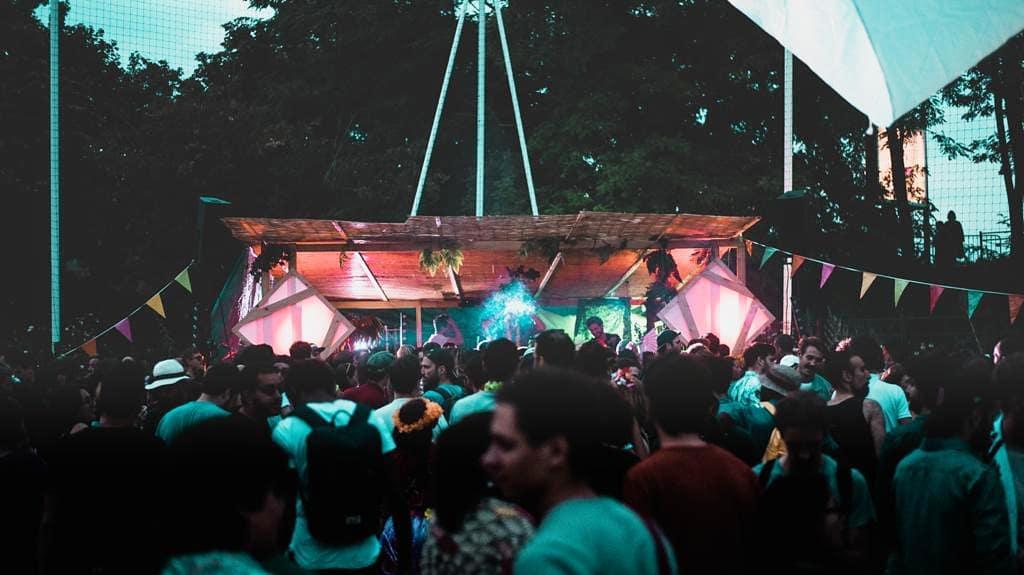 open air au canal barboteur. Lumière de fin de jours. Une foule floue précède une scène en paille sur laquelle des Dj mixent de la musique.