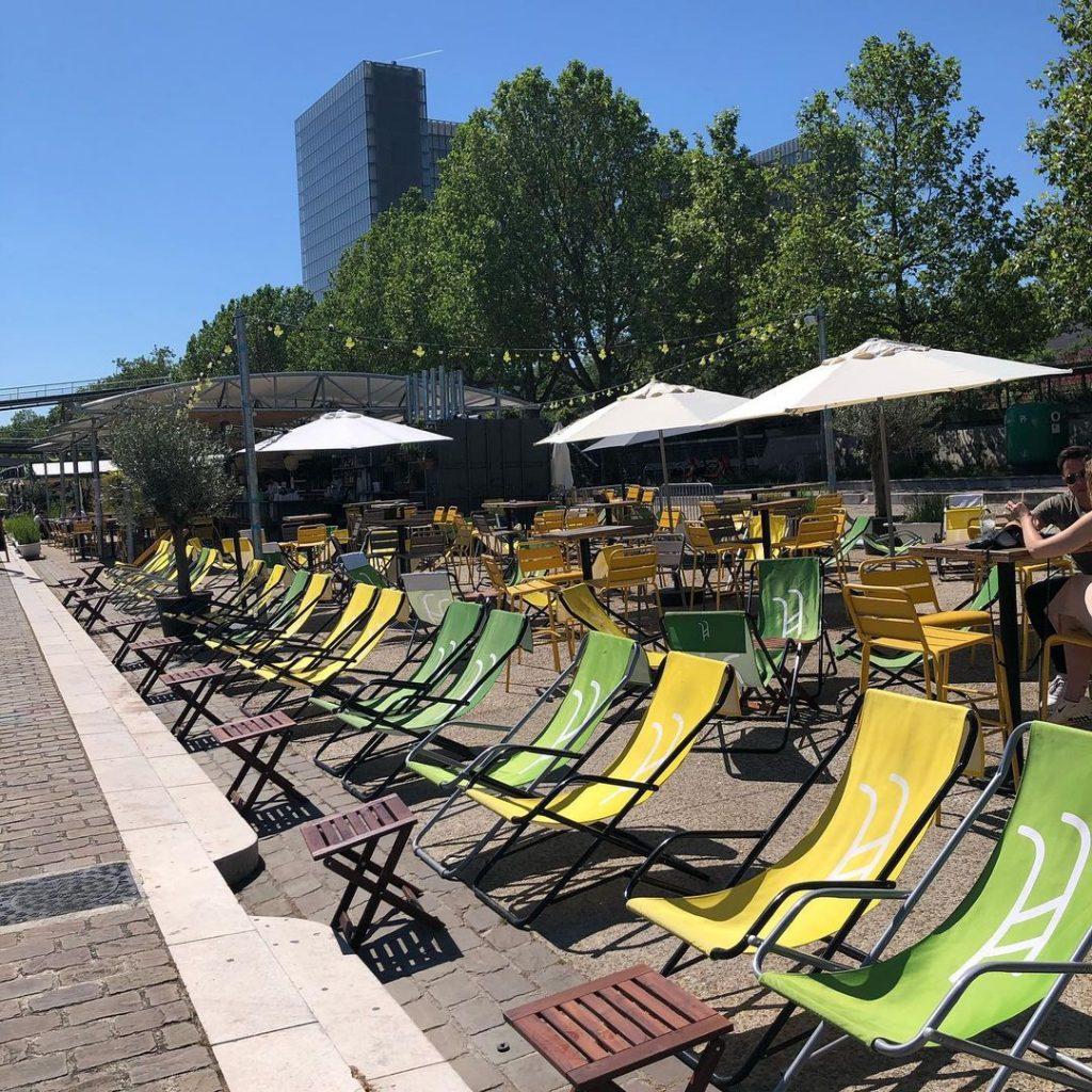 Plan de la terrasse vide de la guinguette du petit bain. Des chaises longue sont posées sur le quai, en rangée devant des tables de cafés.